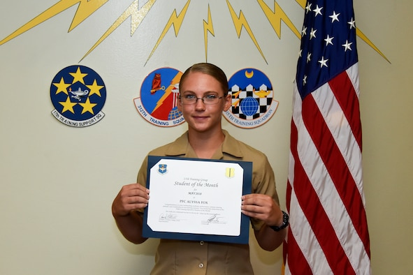 17th Training Group Student of the Month spotlight for May 2018, U.S. Marine Corps Pfc. Alyssa Fox, 316th Training Squadron trainee, hold her award in front of a mural at Brandenburg Hall on Goodfellow Air Force Base, Texas, June 1, 2018. Fox is the Goodfellow Student of the Month spotlight for May 2018, a series highlighting Goodfellow students. (U.S. Air Force photo by Airman 1st Class Zachary Chapman/Released)