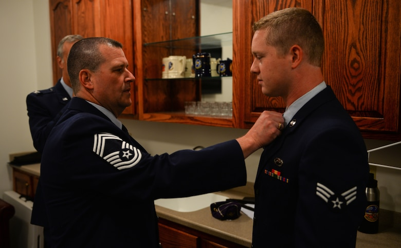 Chief Master Sgt. Allan Turk, 47th Operations Support Squadron radar approach control chief controller, double-checks his son, Senior Airman Mitchel Turk's uniform before the commencement of the chief's retirement ceremony at Laughlin Air Force Base, Texas, June 1, 2018. After serving for 30 years in the Air Force, Turk retires, wishing that he had just one more year to serve beside his wingmen. (U.S. Air Force photo by Senior Airman Benjamin N. Valmoja)