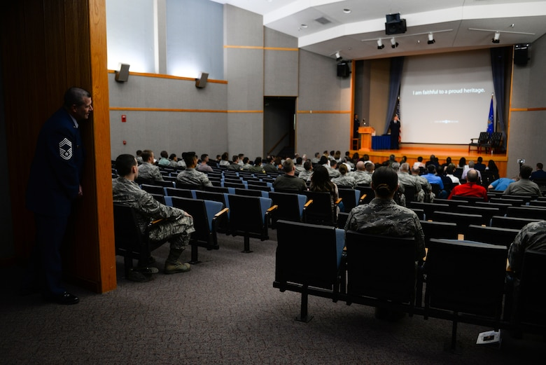 Chief Master Sgt. Allan Turk, 47th Operations Support Squadron radar approach control chief controller, takes a sneak peak of the opening slideshow for his retirement ceremony at Laughlin Air Force Base, Texas, June 1, 2018. Just moments before the official party was introduced to the ceremony, Turk couldn't resist watching the retirement video put together for him on the big screen. (U.S. Air Force photo by Senior Airman Benjamin N. Valmoja)