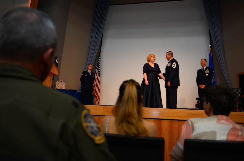 Chief Master Sgt. Allan Turk, 47th Operations Support Squadron radar approach control chief controller, and his wife, Jennifer Turk, embrace after Turk is finally pinned with the retiree lapel pin at Laughlin Air Force Base, Texas, June 1, 2018. Turk retired today after 30 years of faithful service to the Air Force, and spent nearly his entire career side-by-side his wife. (U.S. Air Force photo by Senior Airman Benjamin N. Valmoja)