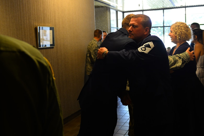 Chief Master Sgt. Allan Turk, 47th Operations Support Squadron radar approach control chief controller, hugs a wingman goodbye after Turk's retirement ceremony at Laughlin Air Force Base, Texas, June 1, 2018. Turk, a self-proclaimed family man, says that he was fortunate and humbled to be able to serve for 30 years in the Air Force, where he considers every Airman family. (U.S. Air Force photo by Senior Airman Benjamin N. Valmoja)