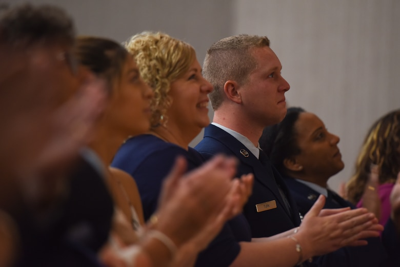 Senior Airman Mitchel Turk, 603rd Air and Space Operations Center, Ramstein Air Base, Germany, watches with pride as the final slides for his father's retirement ceremony make their way across the screen at Laughlin Air Force Base, Texas, June 1, 2018. His father, Chief Master Sgt. Allan Turk, 47th Operations Support Squadron radar approach control chief controller, served for 30 years and has finally retired. (U.S. Air Force photo by Senior Airman Benjamin N. Valmoja)