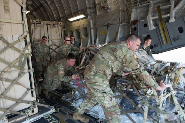 Army Soldiers from the 555th Engineer Brigade and Air Force Airmen from the 4th Airlift Squadron work together to unload a pallet of equipment from a C-17 Globemaster III, May 21, 2018, at Moses Lake, Wash. The Soldiers were moving vehicles and equipment from Joint Base Lewis-McChord to Moses Lake part of a rapid deployment exercise. (U.S. Air Force photo by A1C Sara Hoerichs)