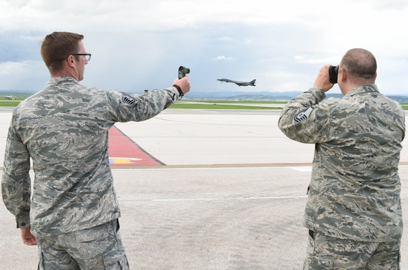 Tech. Sgt. Brandon Williams, the 28th Operations Support Squadron noncommissioned of in charge of airfield weather operations and Master Sgt. William Price 28th OSS Weather Flight chief, use a device that measures wind speed and binoculars to look for approaching weather conditions at Ellsworth Air Force Base, S.D., May 29, 2018. The weather flight helps leaders on base determine the best times to fly are to avoid any complications that could be harmful to aircrew members. (U.S. Air Force photo by Airman 1st Class Thomas Karol)