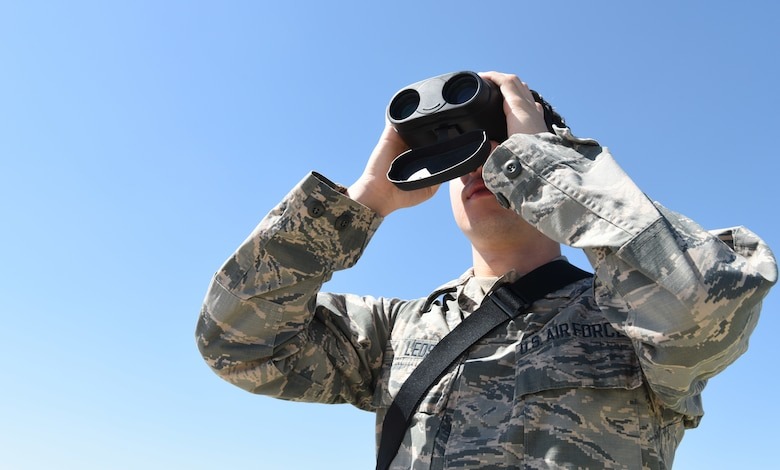 Airman James Leos, 28th Operations Support Squadron weather apprentice, uses a pair of binoculars with a laser range finder to help forecast weather conditions at Ellsworth Air Force Base, S.D, May 30, 2018. The weather flight has to stay on the lookout for changing weather conditions so the flying mission is not affected by any surprise changes in the weather. (U.S. Air Force photo by Airman 1st Class Thomas Karol)