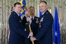 Maj. Gen. Christopher Bence (left), commander of the U.S. Air Force Expeditionary Center, presents Col. Craig Harmon with the 515th Air Mobility Operations Wing guidon as he assumes command of 515th AMOW during a change of command ceremony at Joint Base Pearl Harbor-Hickam, Hawaii, June 1, 2018. 515th AMOW Command Chief Master Sgt. Todd Donaldson is pictured center. Harmon, formerly vice commander of the 515th AMOW, assumed command from Col. Scott Zippwald, who retired after more than 26 years of service in the U.S. Air Force.