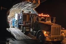 Airmen unload a double recirculating cement mixer trailer.