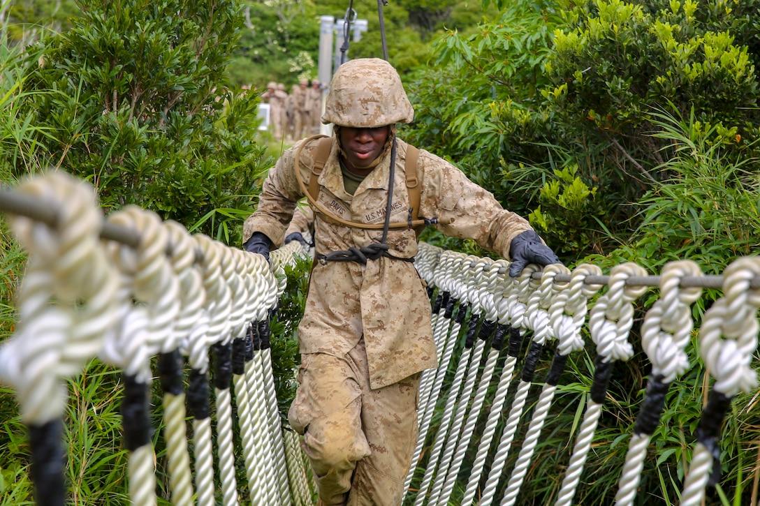 A Marine crosses a rope bridge amid green foliage.