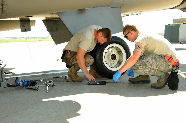 Two Airman inspect a new tire before installing it on an F-16 aircraft