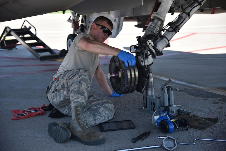 Airman inspects breaks on F-16 aircraft before installing new tire