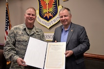 U.S. Rep. Doug Lamborn, presents a copy of the Congressional Record recognizing the Air Force Reserve's 302nd Airlift Wing for its 25 years supporting the Modular Airborne Fire Fighting System mission to Col. James DeVere, the 302nd AW commander, at Peterson Air Force Base, Colorado, June 1, 2018. Lamborn came to the wing on an official visit to discuss the MAFFS mission with DeVere. Lamborn's proclamation was officially added to the U.S. House of Representatives Congressional Record April 26, 2018. (U.S. Air Force photo/Staff Sgt. Frank Casciotta)