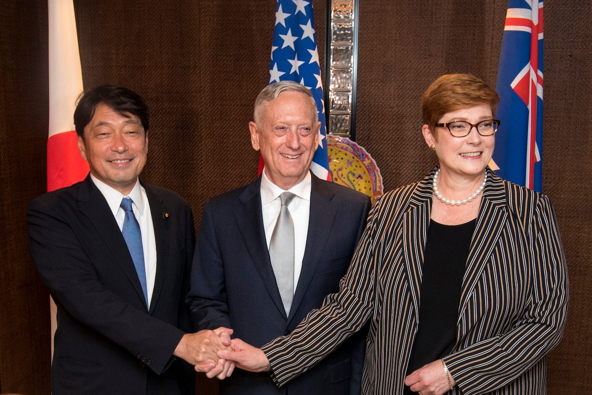 Three defense leaders pose for a photograph with their hands together.