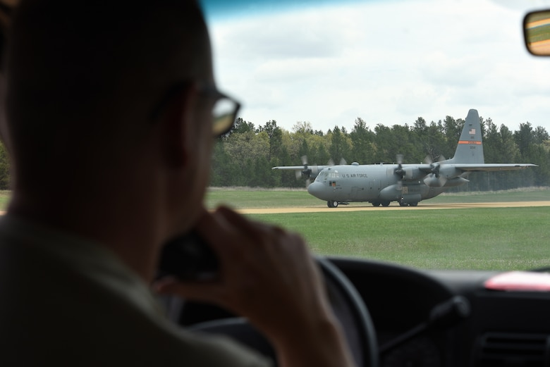 U.S. Air Force Senior Master Sgt. Brent Bixby, an airfield management superintendent with the 182nd Airlift Wing, Illinois Air National Guard, communicates via radio to the pilot of a C-130 Hercules as it taxis at Young Landing Zone at Fort McCoy, Wis. May 14, 2018. A number of pilots were qualifying to complete their unimproved landing certification. (U.S. Air National Guard photo by Master Sgt. Todd A. Pendleton)