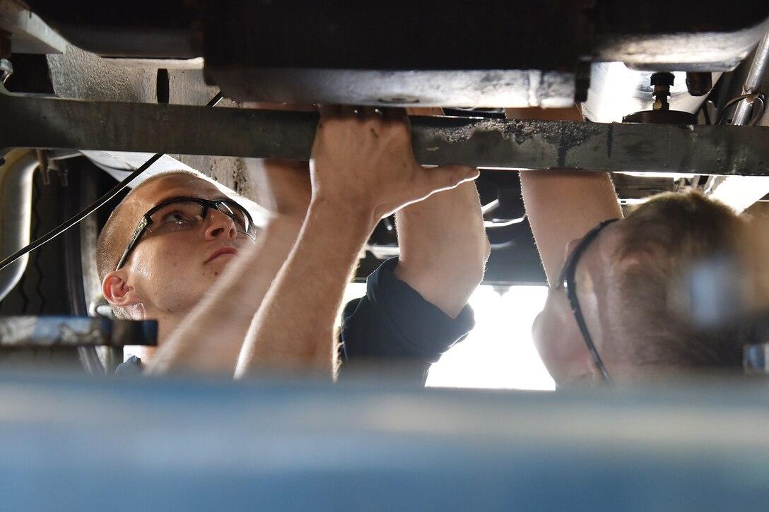 114th Vehicle Maintenance mechanics replacing a transmission filter.