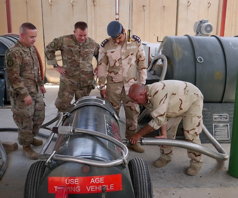 (L-R) Senior Master Sgt. Tim Smith and Master Sgt. Brian Osman, air advisors assigned to the 770th Air Expeditionary Advisory Squadron, and Iraqi Air Force 1st Lt. Alaa Aziz, oxygen officer, watch an Iraqi maintenance airman fill up a tank with liquid oxygen May 22, 2018, at Al Muthana Air Base in Baghdad, Iraq. (U.S. Air Force photo by Capt. Benjamin Hughes)