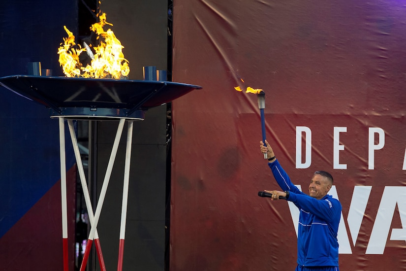 A retired airman lights the torch opening the 2018 Warrior Games.