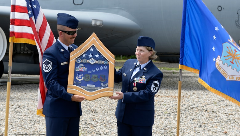Senior Master Sgt. Deborah A Tzrinske receives her shadow box from Master Sgt. Kevin C. Reiter, the 157th Air Refueling Wing administration superintendent, during her retirement ceremony on June 2, 2018 at Pease Air National Guard Base, N.H. Tzrinske served as the 157th ARW first sergeant for more than eight years and retired after more than 28 years of service. (N.H. Air National Guard photo by Staff Sgt. Kayla White)