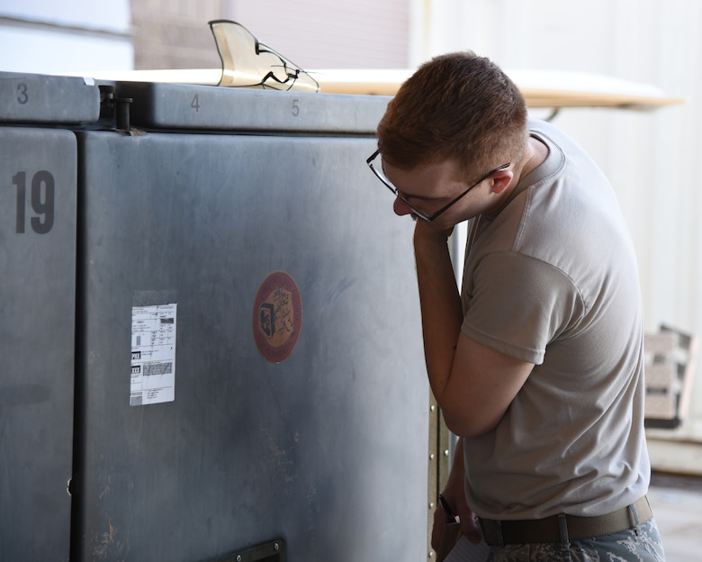 Staff Sgt. Joshua Taylor, an aircrew flight equipment technician with the 161st Air Refueling Wing, inspects the exterior of a shipping container during a cargo pallet preparation class at Goldwater Air National Guard Base, June 3, 2018. Identifying cargo weight and dimensions is a crucial step when determining the proper methods to secure a load for shipping. (U.S. Air National Guard photo by Staff Sgt. Wes Parrell)