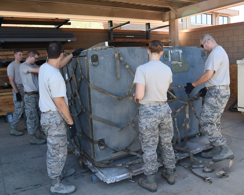 Airmen from the 161st Air Refueling Wing secure a shipping container onto a pallet during a cargo pallet preparation class at Goldwater Air National Guard Base, June 3, 2018. Working as a team insures that the load is properly secured for transportation and that all safety precautions have been made prior to transporting the cargo.  (U.S. Air National Guard photo by Staff Sgt. Wes Parrell)