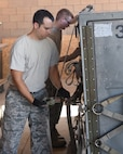 Staff Sgt. Zachary Milne and Staff Sgt. Joshua, aircrew flight equipment technicians with the 161st Air Refueling Wing, secure cargo netting to a pallet during a cargo pallet preparation class at Goldwater Air National Guard Base, June 3, 2018. Properly securing cargo netting and load straps insure that cargo does not shift while being transported. (U.S. Air National Guard photo by Staff Sgt. Wes Parrell)