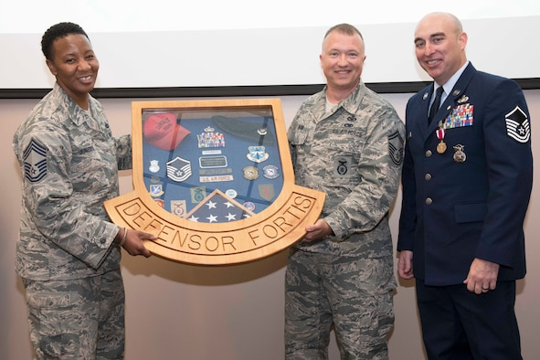 Master Sgt. Lucas Applewhite (right), 403rd Security Forces Squadron senior active reservist and security forces action officer, receives a shadow box with items reflecting various points of his career from security forces members at his retirement ceremony June 2, 2018, at Keesler Air Force Base, Mississippi. Lucas retired from the U.S. Air Force Reserve after serving in the military for 21 years, all of which were with the Air Force and security forces. (U.S. Air Force photo by Tech. Sgt. Ryan Labadens)