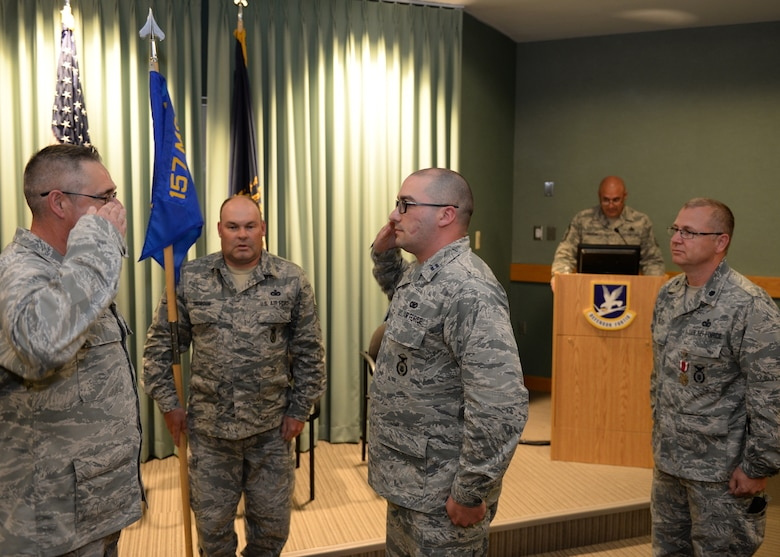 Col. Paul N. Loiselle, 157th Mission Support Group commander, left, exchanges a salute with Capt. Aaron C. McCarthy, 157th Security Forces Squadron incoming commander during a ceremony at Pease Air National Guard Base, N.H., June 2, 2018. Lt. Col. Jassen L. Bluto, far right, outgoing 157th SFS commander, looks on.  (N.H. Air National Guard photo by Staff Sgt. Curtis J. Lenz)