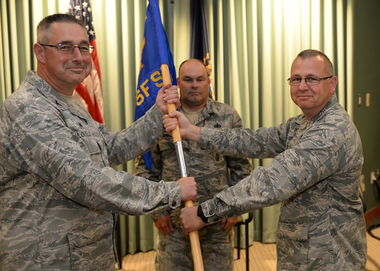 Col. Paul N. Loiselle, 157th Mission Support Group commander, left, receives the 157th Security Forces Squadron guidon from outgoing Lt. Col. Jassen L. Bluto, 157th SFS outgoing commander, during a change of command ceremony at Pease Air National Guard Base, N.H., June 2, 2018. Pluto initially took command of the squadron in 2010. (N.H.. Air National Guard photo by Staff Sgt. Curtis J. Lenz)