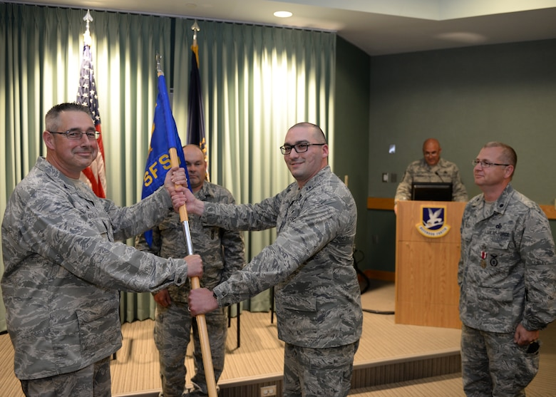 Col. Paul N. Loiselle, 157th Mission Support Group commander, left, receives the 157th Security Forces Squadron guidon from Capt. Aaron C. McCarthy, 157th SFS incoming commander during a ceremony at Pease Air National Guard Base, N.H., June 2, 2018.  McCarthy assumed command of the squadron from Lt. Col. Jassen L Bluto, outgoing commander.  (N.H. Air National Guard photo by Staff Sgt. Curtis J. Lenz)