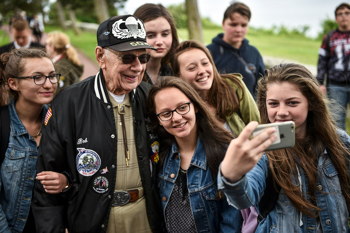 A World War II veteran smiles for a selfie with a group of schoolgirls.
