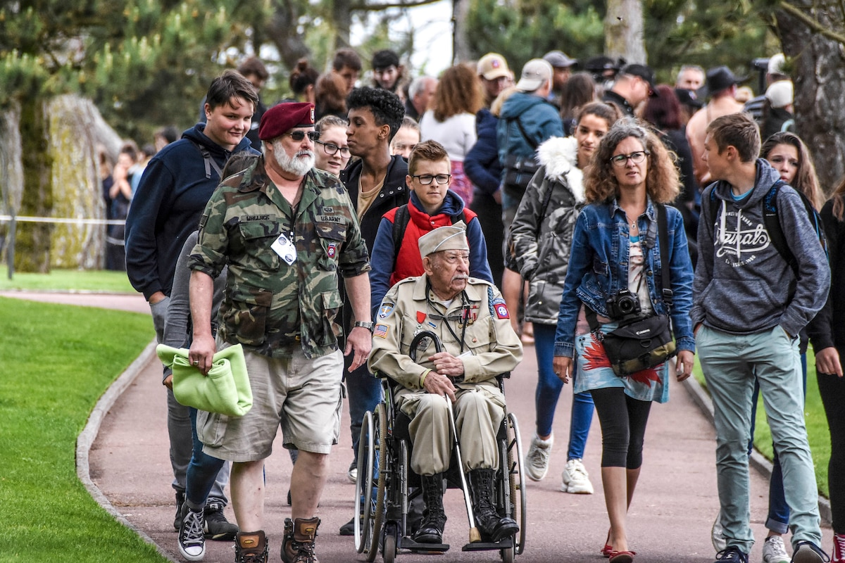 Family members walk with a World War II veteran, who wears his uniform and sits in a wheelchair, on an outdoor path.