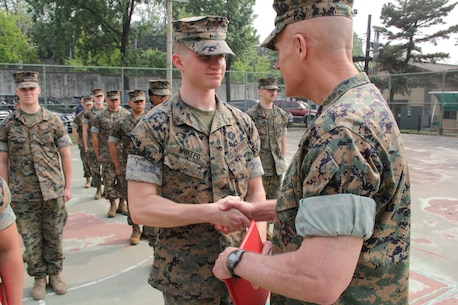 Lance Cpl. Marcus A. Whited (left), U.S. Marine Corps Forces Korea G6 help-desk clerk, is congratulated before receiving a Certificate of Commendation from Maj. Gen. Patrick J. Hermesmann, MARFORK commander, during a ceremony here, May 14. Whited was selected Marine of the Quarter for performing above his peers. (U.S. Marine Corps photo by Staff Sgt. Anthony Kirby/Released)