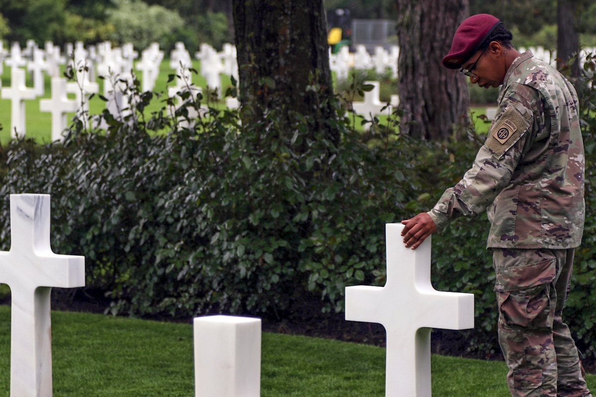 A soldier touches and looks down on a cross-shaped gravestone in a cemetery of identical stones.