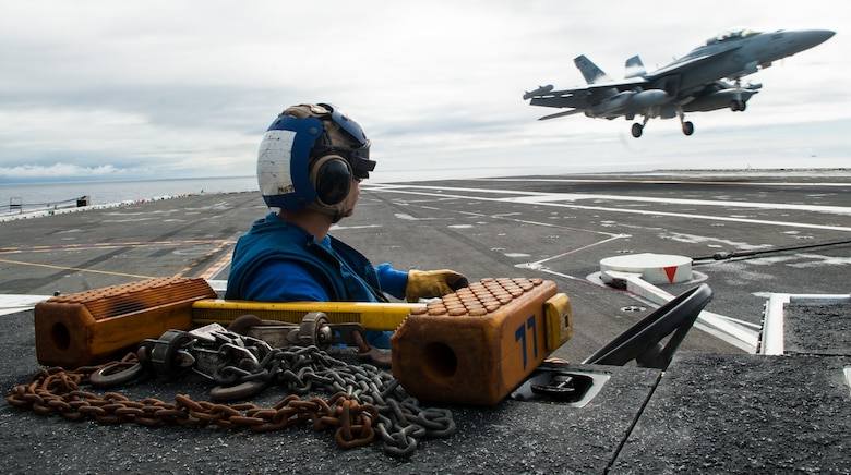 Aviation Boatswain's Mate Airman Alexander Dooley, from Bradenton, Florida, observes an EA-18G Growler, assigned to Strike Fighter Squadron (VAQ) 141, as it lands on the flight deck during carrier qualifications with the Navy's forward-deployed aircraft carrier, USS Ronald Reagan (CVN 76), and Carrier Air Wing 5. Ronald Reagan, the flagship of Carrier Strike Group 5, provides a combat-ready force that protects and defends the collective maritime interests of its allies and partners in the Indo-Pacific region.