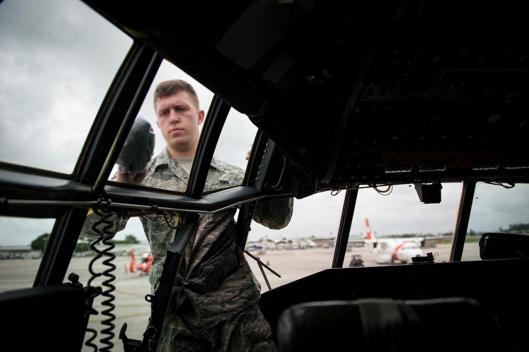 """Air Force Reserve Senior Airman  Spencer Kalapp, crew chief, 720th Aircraft Maintenance Squadron from Patrick Air Force Base in Cocoa Beach, Florida, cleans the windshields of an HC-130- P/N """"King"""" on May 25th, 2018, at Miami, before a practice run for the 2nd annual Salute to American Heroes Air and Sea Show. This two-day event showcases military fighter jets and other aircraft and equipment from all branches of the United States military in observance of Memorial Day, honoring servicemembers who have made the ultimate sacrifice. (U.S. Air Force photo/Staff Sgt. Jared Trimarchi)"""