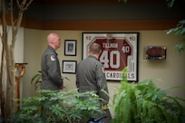 Team Dover members look at the Pat Tillman jersey on display at AFMAO.