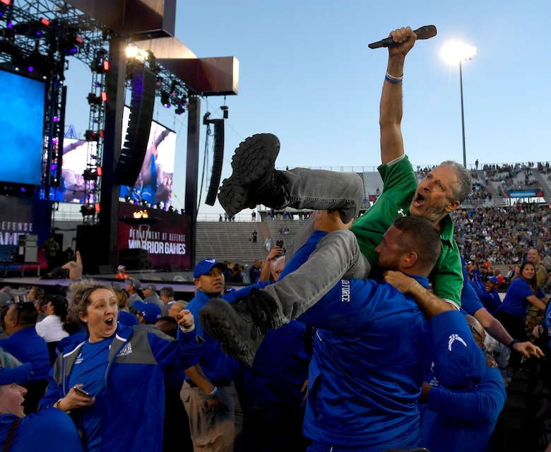 Actor and television personality Jon Stewart is hoisted up in the air by members of Team Air Force during the opening ceremony of the Department of Defense Warrior Games at the U.S. Air Force Academy in Colorado Springs, Colorado, June 2, 2018. First held in Colorado Springs in 2010, the Warrior Games were established as a way to expose service members who were wounded, ill or injured to adaptive sports. The Air Force is the host service for this year's Games. (U.S. Air Force photo by Staff Sgt. Rusty Frank)