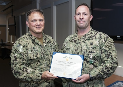 Naval Surface Warfare Center Panama City Division (NSWC PCD)Commanding Officer Capt. Aaron Peters, USN, left, congratulates Navy Diver Chief (DSW/EXW/SW) Taylor Arney, USN, right, on receiving the Navy and Marine Corps Commendation Medal for his meritorious service while serving as research, development, testing, and evaluation diving operations chief and assistant production officer at NSWC PCD. U.S. Navy photo by Eddie Green