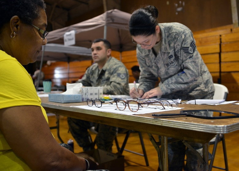 U.S. Air Force Staff Sgt. Jay Griggs (left) assigned to the Aeromedical Staging Squadron and Staff Sgt. Leslie Hamill assigned to the 166th Medical Group, acting medical technician augmentees, assist optometry patients with selecting eyeglasses during Operation Empower Health - Savannah at the Garden City Recreational Center, Garden City, Ga., May 10, 2018. (U.S. Air National Guard photo by Senior Airman Jamila A. Haven)