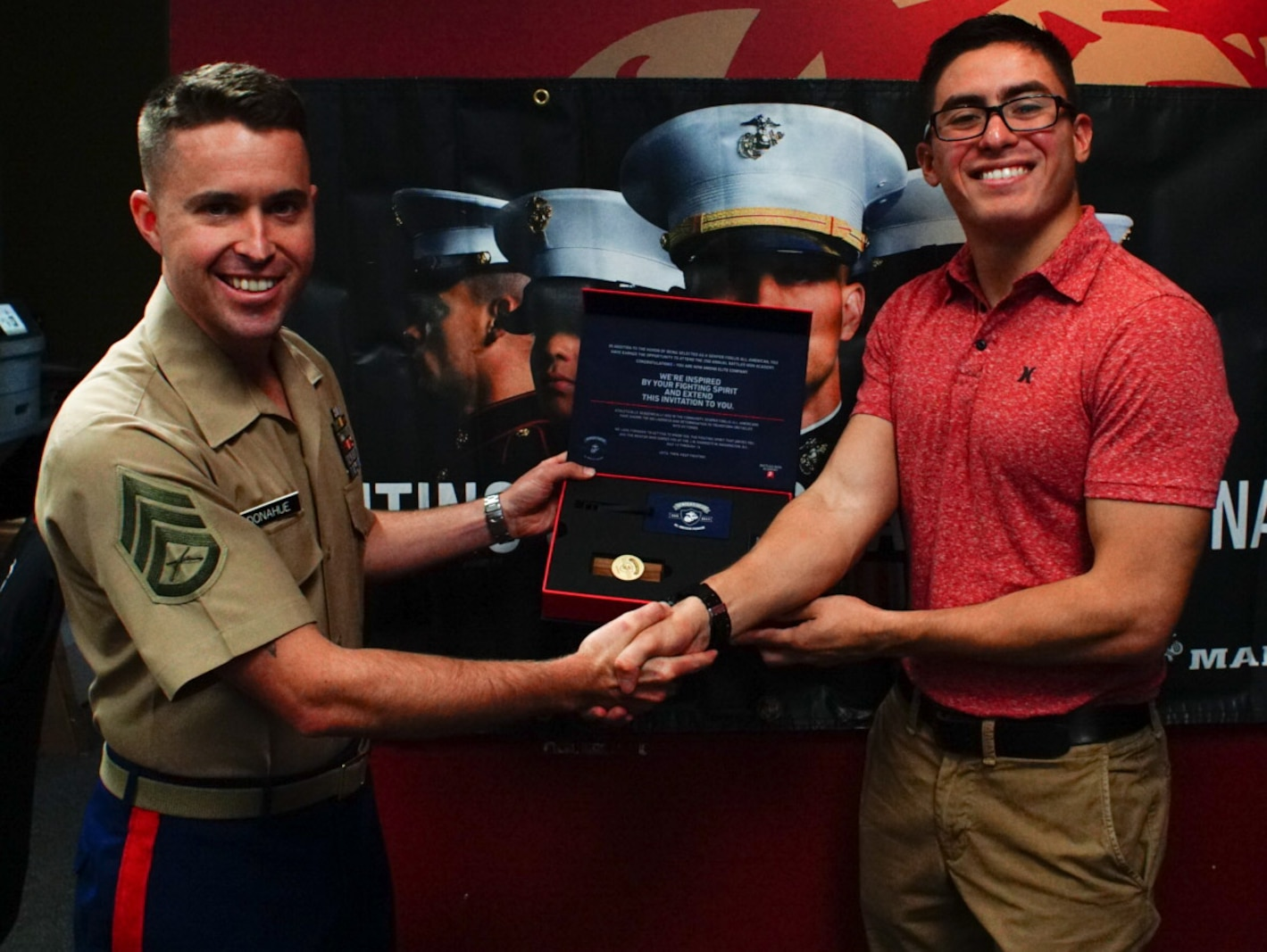 SSgt. Michael Donahue, recruiter from recruiting substation Wesley Chapel, presents Nicholas Verstegui his Semper Fi All American Program invitation kit at RSS Wesley Chapel, Florida, June 1, 2018.