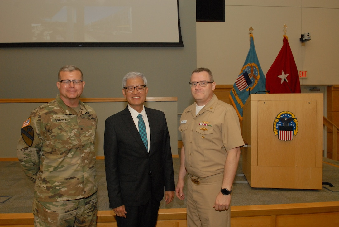 DLA Troop Support Commander Army Brig. Gen. Mark Simerly, left, poses with Asian American Pacific Islander Heritage Month event guest speaker Timothy Haahs, an architect, engineer and entrepreneur, and NAVSUP Weapons Systems Support Deputy Commander Navy Capt. David Ludwa May 24, 2018. During the event Haahs discussed his experiences growing up in a leper colony in South Korea, coming to the U.S. when he was 12 years old, receiving two heart transplants and becoming a U.S. Senate confirmed appointee to the Board of Directors of the National Institute of Building Sciences. Photo by Ed Maldonado