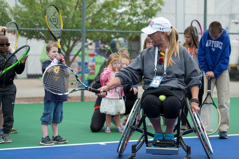 A person in a wheel chair shows children how to old a racket.