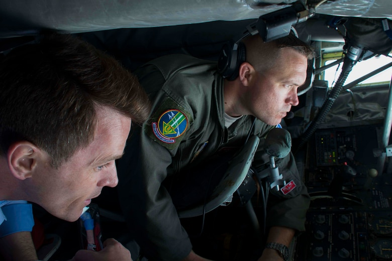 Dan Jovic with KTAL News and Staff Sgt. Patrick Bartosavage, 18th Air Refueling Squadron boom operator, stare through the observation window of a KC-135 Stratotanker after taking off from Barksdale Air Force Base, Louisiana, May 30, 2018.  Jovic and 29 other civic leaders from the Greater Shreveport/Bossier City area took part in a tour to Niagara Falls Air Reserve Station, New York to learn about different aspects of the Air Force mission.  These tours are designed to promote understanding of the military and introduce civilian leaders to other military units they may not otherwise see. (U.S. Air Force photo by Master Sgt. Ted Daigle/released)