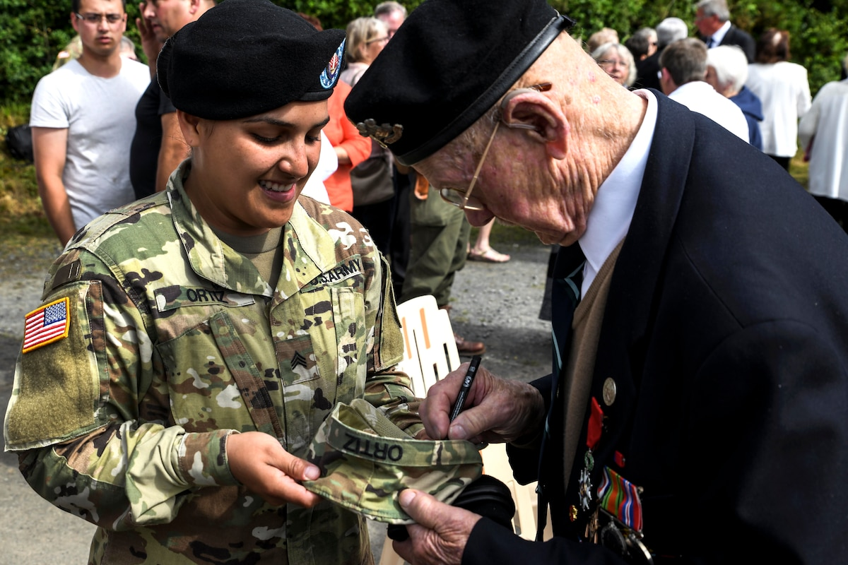 A soldier smiles as a veteran signs her cap.