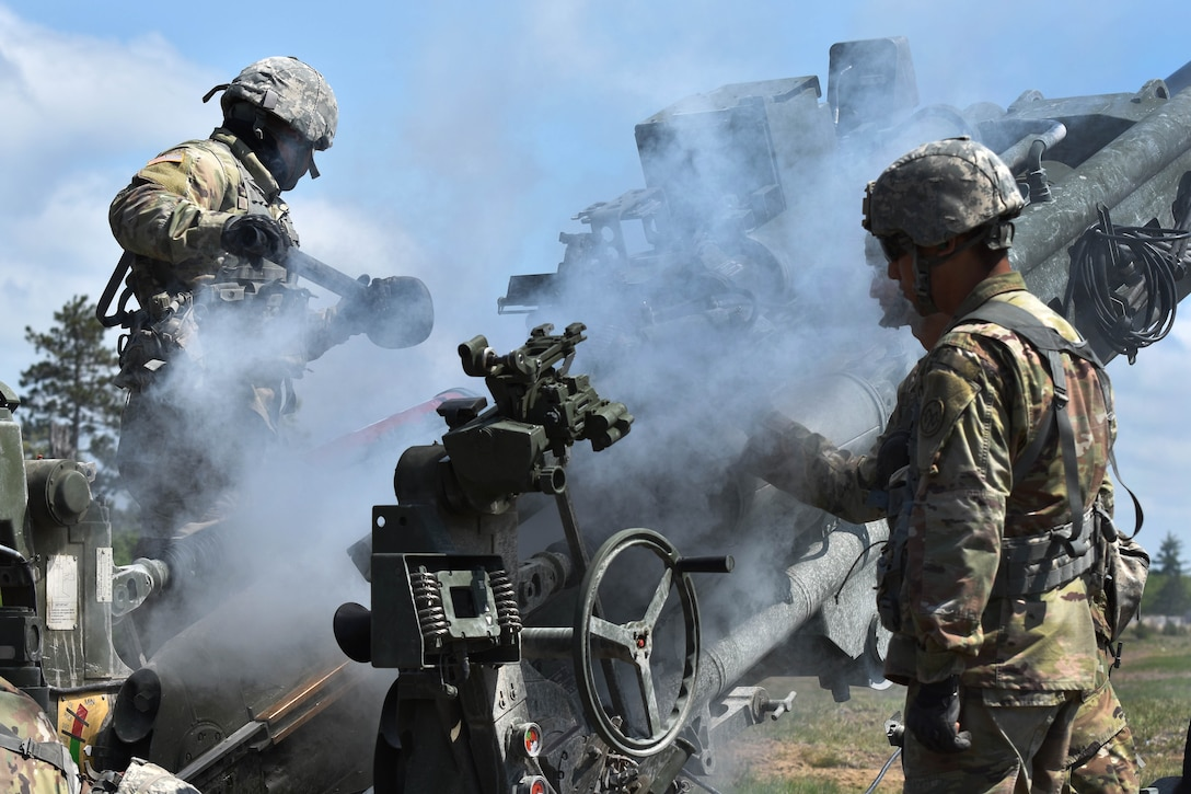 Soldiers clear a M777 howitzer after conducting a live-fire mission.