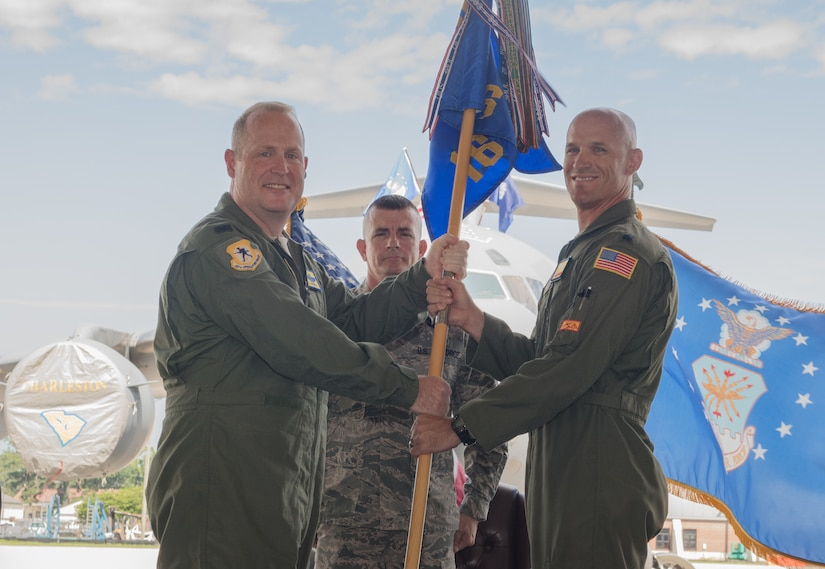 Lt. Col. Alex Pelbath, right, accepts the 16th Airlift Squadron guidon from Col. Louis Hansen, 437th Operations Group commander, during a change of command ceremony in Nose Dock 2 June, 1, 2018.