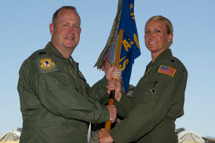 Lt. Col. Kari Fleming, right, accepts the 14th Airlift Squadron guidon from Col. Louis Hansen, 437th Operations Group commander, during a change of command ceremony in Nose Dock 2 June 4, 2018.