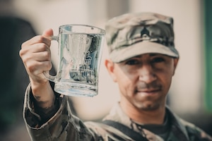 Army Sgt. Daniel Baudoin, a water purification specialist with the 240th Composite Supply Company of Baumholder, Germany, displays his battalion crest and freshly purified water he and his team produced in Poland during Exercise Saber Strike.