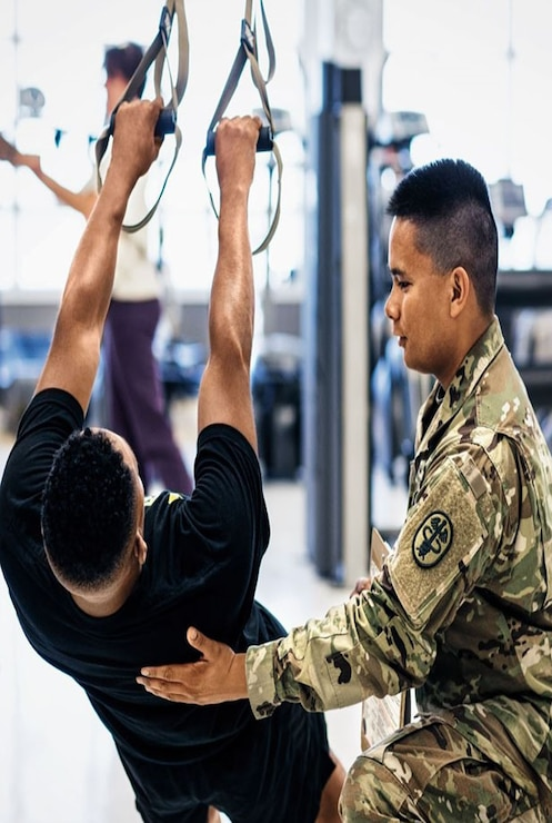Asian male Physical Therapist wearing OCP training with a male ROTC Cadet wearing APFU inside during the daytime.