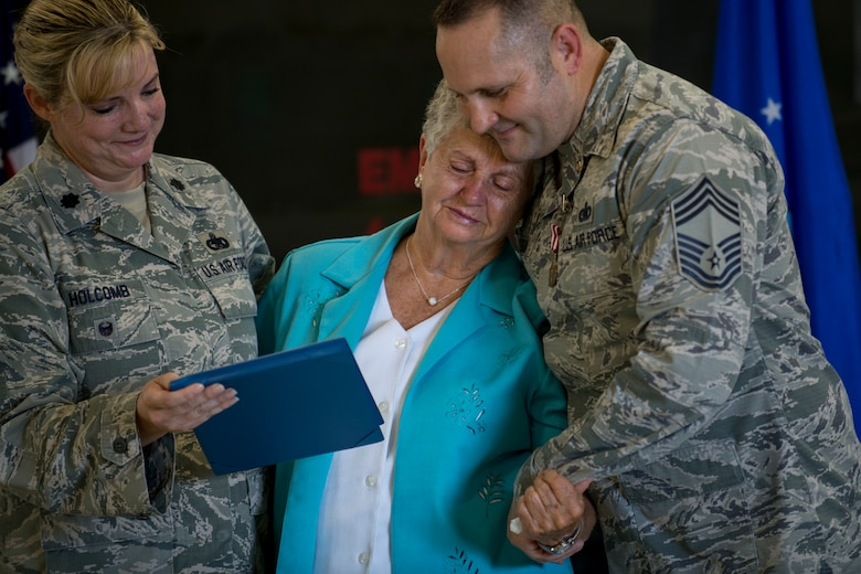 Lt. Col. Laura Holcomb, Calhoun's former commander, presents his mother, Mildred, an award during Chief Master Sgt. Jim Calhoun 's retirement ceremony, June 1, 2017, at Moody Air Force Base, Ga. Calhoun entered the Air Force in August of 1991 and served in numerous positions within fuels management and logistics readiness throughout his career. (U.S. Air Force photo by Senior Airman Daniel Snider)