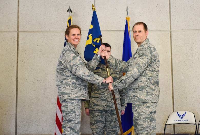 Lt. Col. David Jackson, the new 419th Medical Squadron commander, accepts the squadron flag from Col. Regina Sabric, 419th Fighter Wing commander, during a change of command ceremony